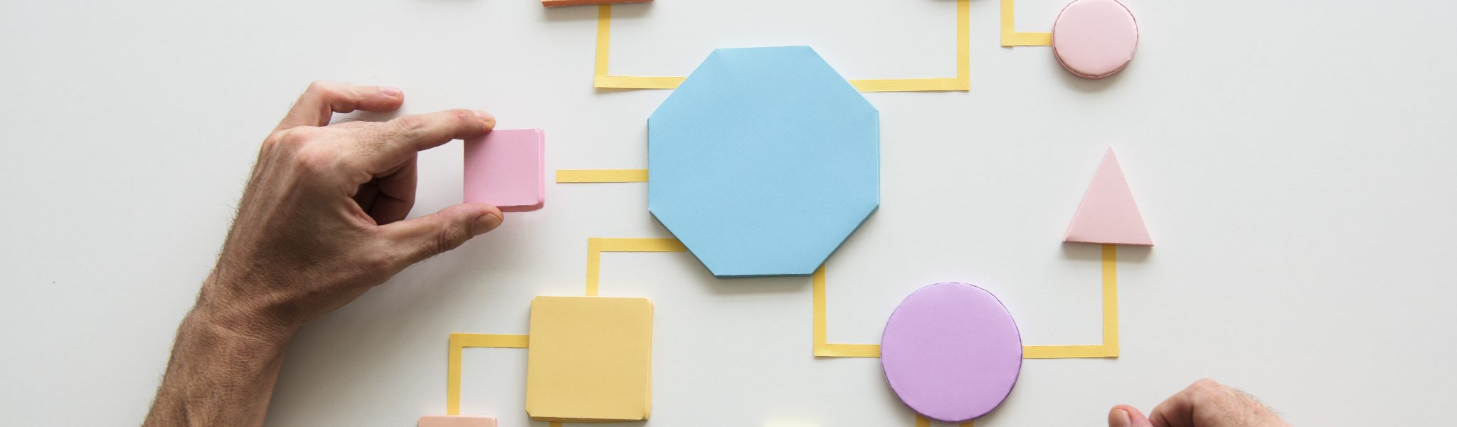 Man adding a box to a CX strategy made of shapes