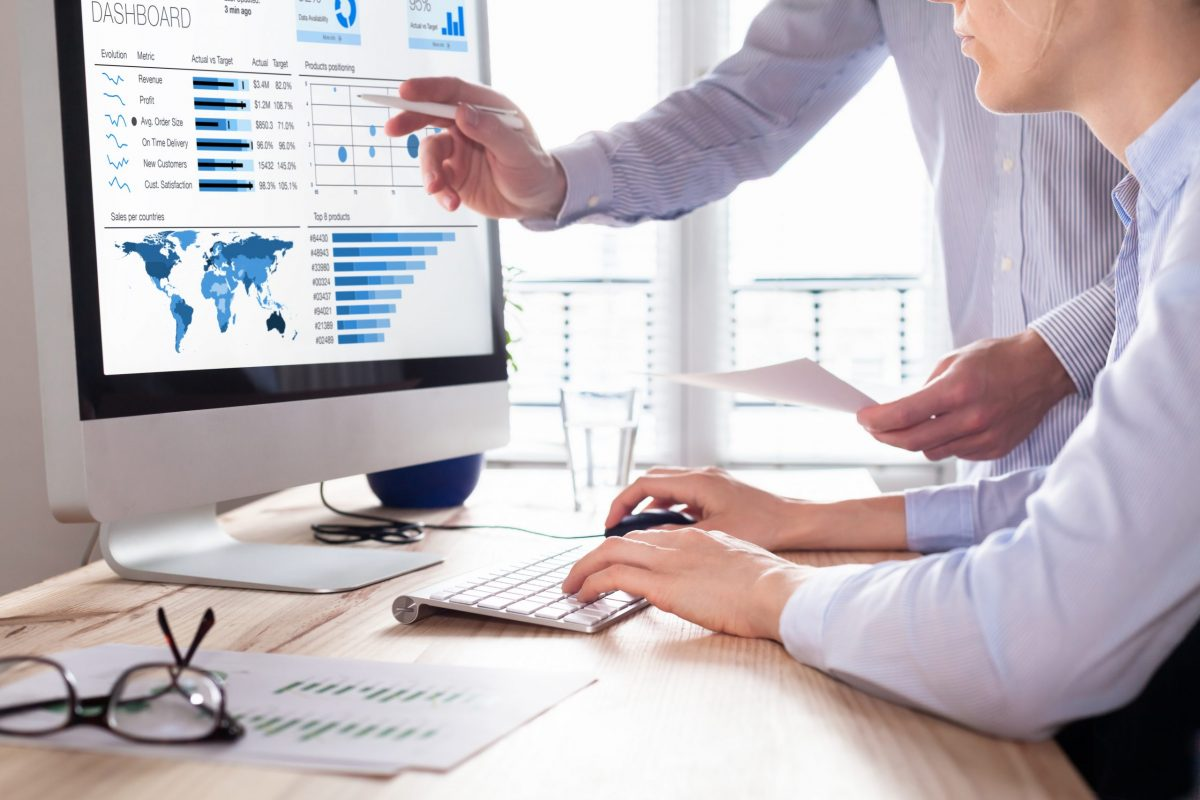 Man and woman examining data quality of analytics on a dashboard